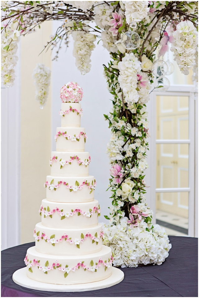 Queen of Romance - A very tall and grand cake adorned with swags of white and pink sugar flowers with a pomander topper.