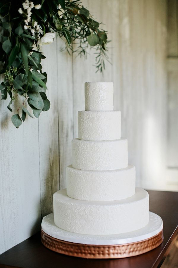 white wedding cake with copper cake stand